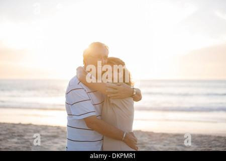 Senior couple hugging on beach - Stock Photo