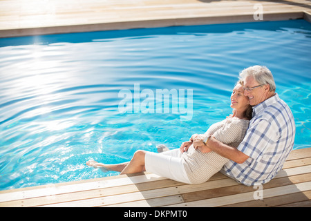 Senior couple relaxing by pool - Stock Photo