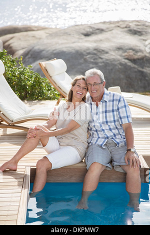 Older couple relaxing by swimming pool - Stock Photo