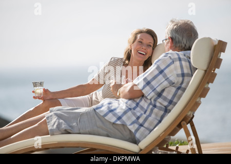 Older couple relaxing in lawn chairs - Stock Photo
