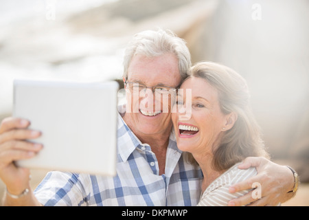 Older couple taking pictures with digital tablet - Stock Photo
