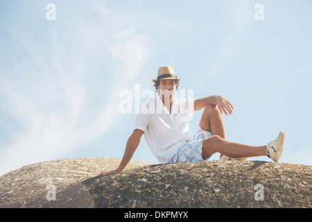 Man sitting on rock formation - Stock Photo