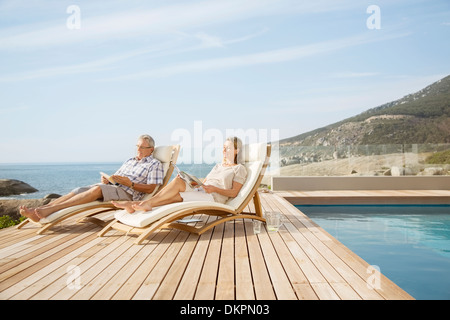 Older couple relaxing by pool - Stock Photo