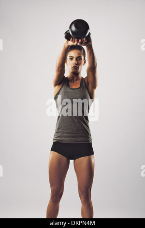 Pretty young woman swinging kettle bell weight with both hands. Crossfit female working out on grey background - Stock Photo