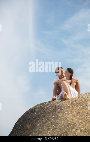 Couple relaxing on rock formation - Stock Photo