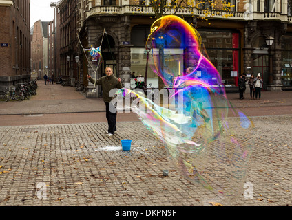AMSTERDAM HUGE SOAP BUBBLES BLOWING IN THE STREET MADE BY A BUBBLE BLOWER AND HIS BUCKET OF SOAP SUDS - Stock Photo