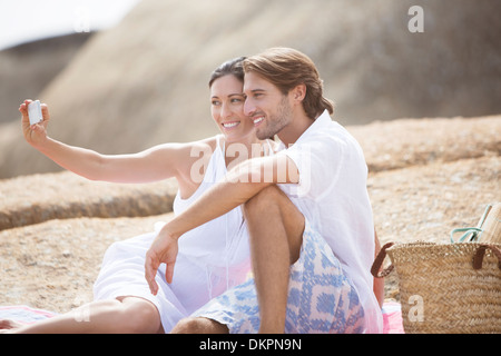 Couple taking pictures together on sandy beach - Stock Photo