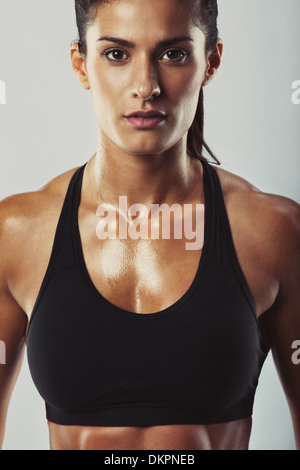 Close up image of young woman in sports bra looking at camera against grey background. Muscular build female relaxed - Stock Photo