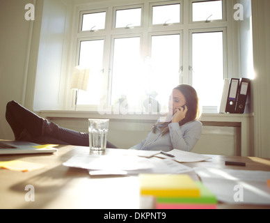 Young woman sitting at her table with legs on desk talking on mobile phone. Caucasian businesswoman using cell phone. - Stock Photo