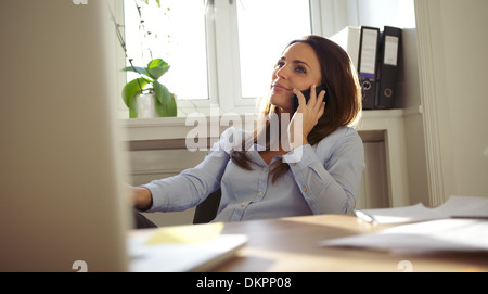 Attractive young woman sitting at her desk talking on mobile phone. Pretty caucasian businesswoman working in home - Stock Photo