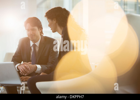 Business people using laptop in office - Stock Photo