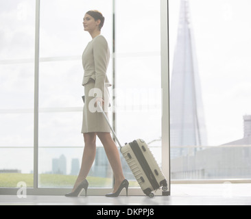 Businesswoman rolling suitcase in airport - Stock Photo