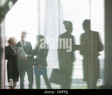 Reflection of business people talking in office - Stock Photo