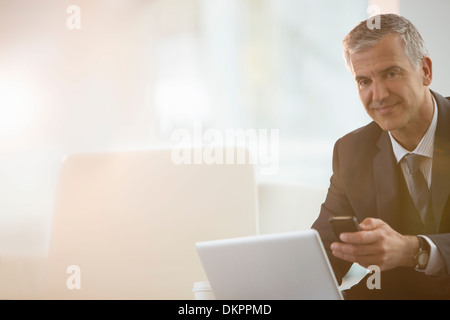 Businessman using cell phone and laptop in office - Stock Photo
