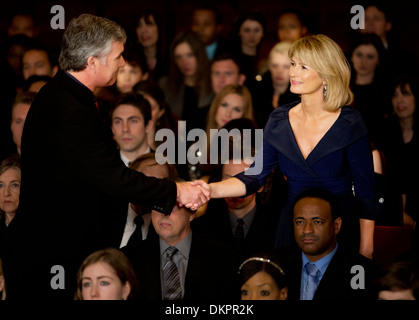 Man and woman handshaking in theater audience - Stock Photo