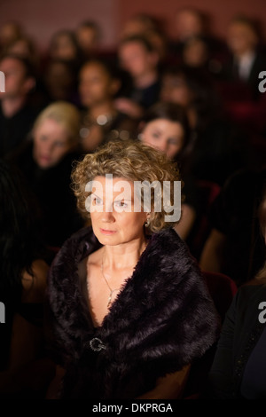Serious woman in theater audience - Stock Photo