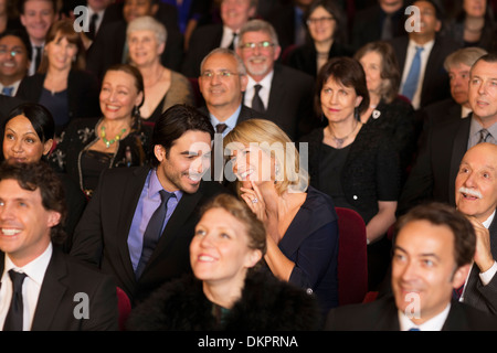 Happy couple clapping in theater audience - Stock Photo