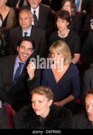 Man laughing among serious theater audience - Stock Photo