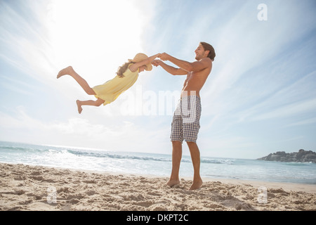 Father and daughter playing on beach - Stock Photo