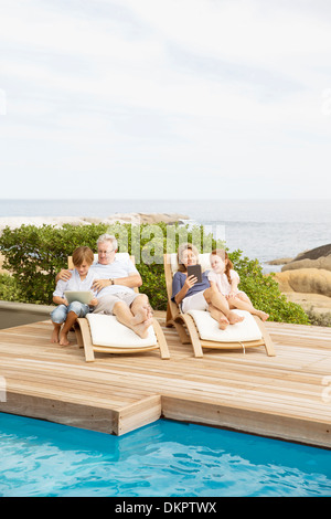 Older couple and grandchildren relaxing by pool - Stock Photo