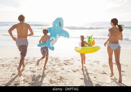 Family playing together on beach - Stock Photo