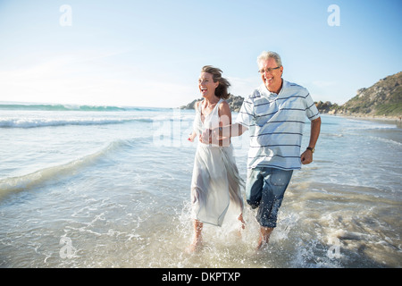 Older couple playing in waves on beach - Stock Photo
