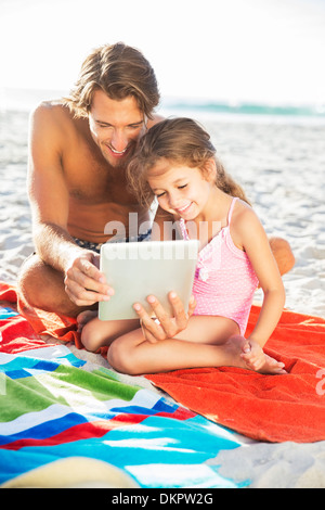 Father and daughter using digital tablet on beach - Stock Photo