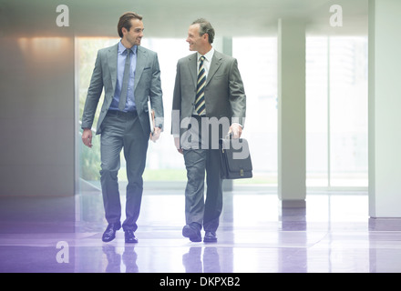 Businessmen talking in office lobby - Stock Photo