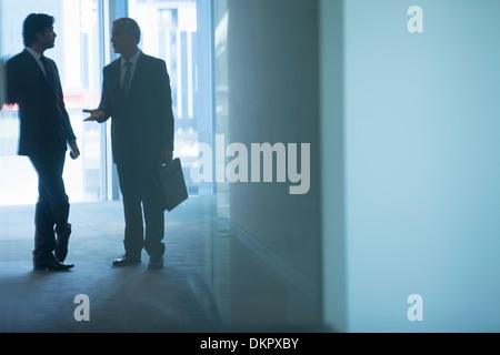 Businessmen talking in office corridor - Stock Photo