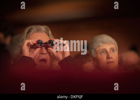Close up of man using opera glasses in theater - Stock Photo