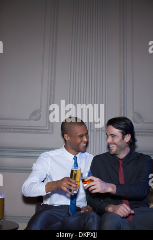 Well dressed men toasting beer and cocktails - Stock Photo
