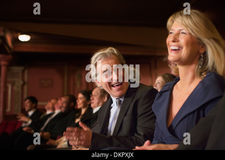 Couple laughing and clapping in theater - Stock Photo