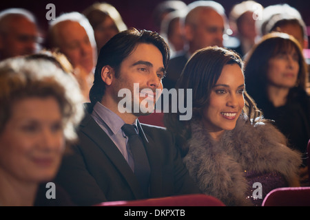 Close up of smiling couple in theater audience - Stock Photo