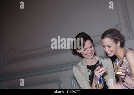 Well dressed women drinking champagne and looking at cell phone - Stock Photo
