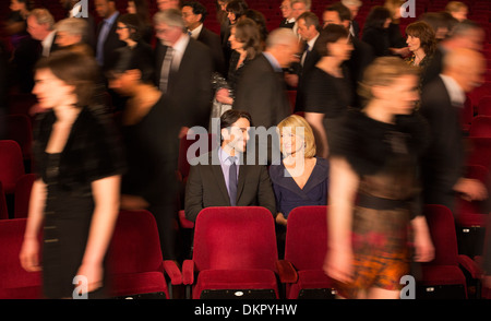 Couple sitting among people leaving theater - Stock Photo