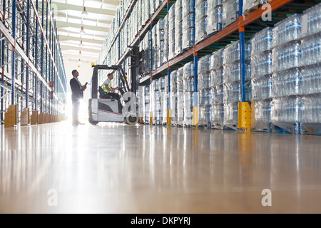 Workers with forklift in bottling warehouse - Stock Photo