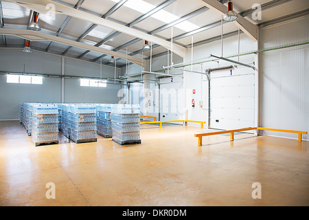 Pallets of water bottles in empty warehouse - Stock Photo
