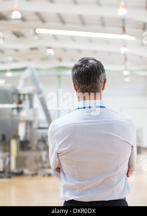 Businessman standing in factory - Stock Photo