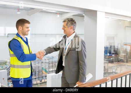 Supervisor and worker shaking hands in factory - Stock Photo