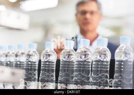 Supervisor examining bottles in factory - Stock Photo