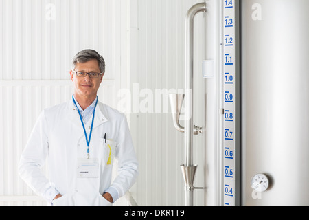 Scientist smiling in food processing plant - Stock Photo
