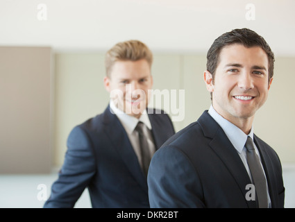 Businessmen smiling in office - Stock Photo