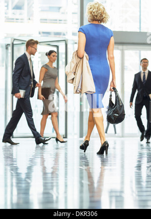 Business people walking in office lobby - Stock Photo