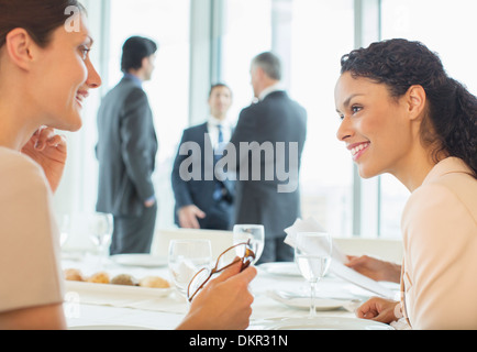 Businesswomen talking in restaurant - Stock Photo