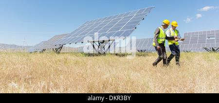 Workers walking by solar panels in rural landscape - Stock Photo