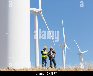 Workers talking by wind turbines in rural landscape - Stock Photo