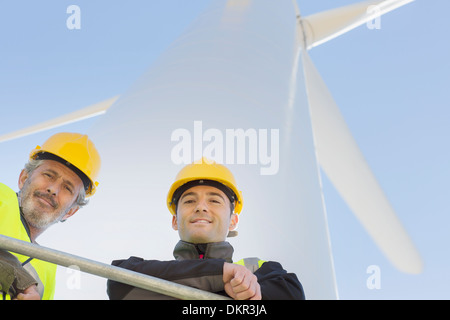 Workers standing on wind turbine in rural landscape - Stock Photo