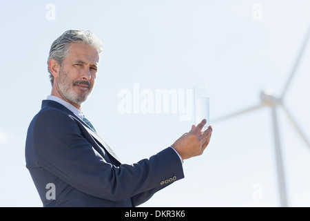 Businessman with glass of water by wind turbine - Stock Photo
