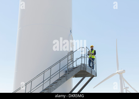 Worker standing on wind turbine - Stock Photo