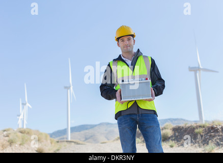 Worker standing by wind turbines in rural landscape - Stock Photo